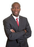 African businessman with crossed arms smiling at camera Stock Photo