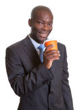 African businessman in a dark suit drinking coffee Royalty Free Stock Images