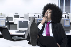 African businessman is daydreaming in the office. Image of African businessman daydreaming with laptop and his foot on the table while sitting in the office Royalty Free Stock Images