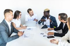 African businessman explaining sales graph to colleagues in meeting. Project summ. African businessman explaining sales graph to colleagues in meeting stock photos