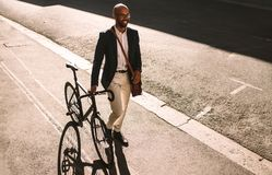 African businessman going office with his bike royalty free stock image