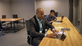African businessman and his colleague working late at night in their office with laptop stock footage