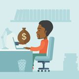 African businessman with his laptop. African Businessman sitting infront of his table working at a laptop searching and browsing with bag of money on hand inside Stock Images