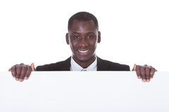 African businessman holding placard. Portrait Of An African Businessman Presenting Blank Placard Over White Background Stock Photos