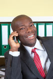 African businessman laughing at phone Stock Photo