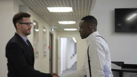 African businessman is meeting his caucasian male partner is the office hall. Multiathnic men are shaking hands and going to the co-working room to discuss the stock footage