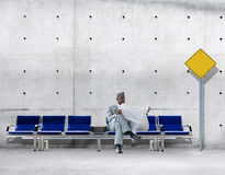 African Businessman Reading Newspaper Waiting Transportation. Concept Stock Photography