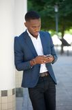 African businessman sending text message on mobile phone Royalty Free Stock Images