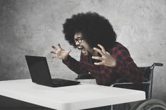 African businessman shouting at his laptop. Portrait of angry african businessman shouting at his laptop while sitting on the wheelchair Stock Photography