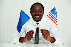 African businessman sitting at the table. And holding USA and European flags royalty free stock photo