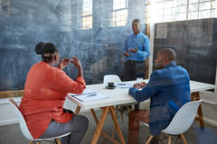 African businessman taking questions from coworkers during presentation. Focused young African businessman taking questions from coworkers while giving a royalty free stock photos