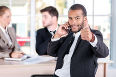 African businessman talking on his mobile phone and showing thumb up. Three successful business people sitting in the office and royalty free stock image