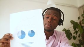 African businessman talking by videocall, showing document stats at webcam stock video footage