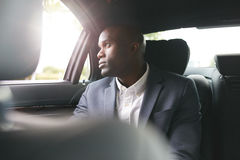 African businessman traveling to work in the luxury car Royalty Free Stock Images