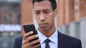 African Businessman Using Smartphone for Browsing online royalty free stock photography