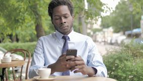 African Businessman Using Smartphone Sitting in Outdoor Cafe stock footage