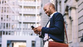 African Businessman Walking Outdoors With Mobile Phone Stock Images