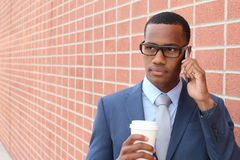 African businessman walking with to go tea cup on the phone with copy space Royalty Free Stock Photo