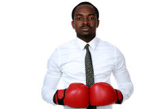 African businessman wearing boxing gloves. Portrait of a serious african businessman wearing boxing gloves over white background Stock Photo