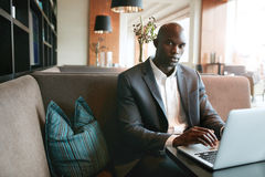 African businessman working on laptop in coffee shop. Portrait of young african businessman working on laptop in cafe. man sitting on hotel coffee shop Stock Photography