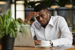 African businessman working with laptop, decided problem. View of young african businessman looking at laptop, thinking, decided problem, have a stress Stock Image