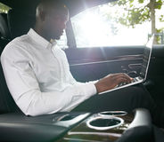 African businessman working on laptop inside a car Royalty Free Stock Photography