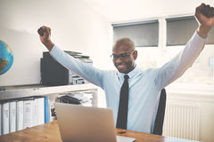 African businessman working on a laptop in an office cheering Stock Photo