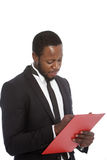 African businessman writing notes on a clipboard Royalty Free Stock Photography