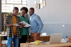 African businesspeople talking together over paperwork in a modern office. Three casually dressed young African work colleagues discussing paperwork together Royalty Free Stock Images
