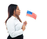 African businesswoman blowing on US flag Royalty Free Stock Image