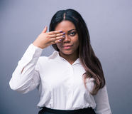 African businesswoman covering one eye with hand Stock Photos
