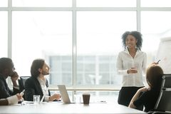 African businesswoman giving presentation working with flipchart. In meeting room making business offer to partners, black women reporting about work result on stock images