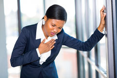 African businesswoman heart attack. Young african american businesswoman having heart attack or chest pain Royalty Free Stock Images