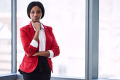 African businesswoman looking into camera confidently while wearing red blazer. Confident businesswoman looking at the camera with bold body language while stock images
