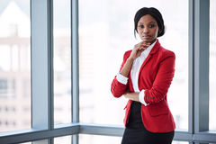 African businesswoman looking into camera confidently while wearing red blazer. Confident businesswoman looking at the camera with bold body language while royalty free stock image
