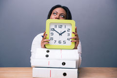 African businesswoman sitting at the table with clock Stock Image