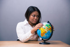 African businesswoman sitting at the table with globe Stock Image