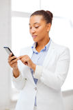 African businesswoman with smartphone in office Royalty Free Stock Images