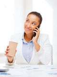 African businesswoman with smartphone in office Stock Photo