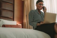 African businesswoman on tour working from hotel room royalty free stock photography