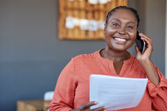 African businesswoman using a cellphone and reading documents at work. Portrait of a smiling young African businesswoman reading paperwork and talking on a stock images