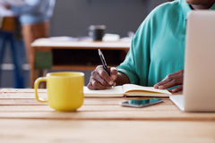 African businesswoman writing notes at her desk in an office. Closeup of an African businesswoman working on a laptop and writing down notes in a book while Royalty Free Stock Photos