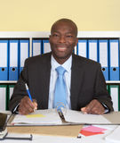 African businssman with blue tie at office writing note Stock Photo