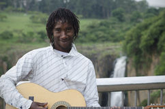 African busker in front of Howick Falls Royalty Free Stock Image