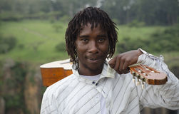 African busker with guitar on shoulder Stock Photography