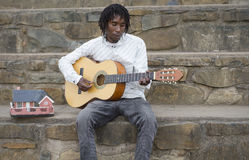 African busker on stone stairs Royalty Free Stock Photos