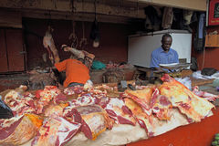 African Butcher Shop. KAMPALA, UGANDA - SEPTEMBER 29 2012.  Two African men work and prepare meat in a dirty open air market in Kampala, Uganda on September 28 Stock Images