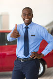 African car salesman. Happy young african car salesman thumb up in showroom royalty free stock photo
