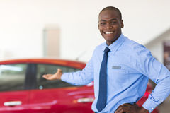 African car salesman. Standing at showroom presenting new cars stock photography