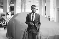 African car salesman using smart phone in showroom. Happy african car salesman using smart phone in showroom royalty free stock photography